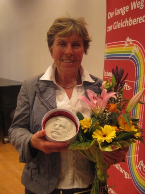 Dagmar Schultz with her Magnus Hirschfeld medal and flowers